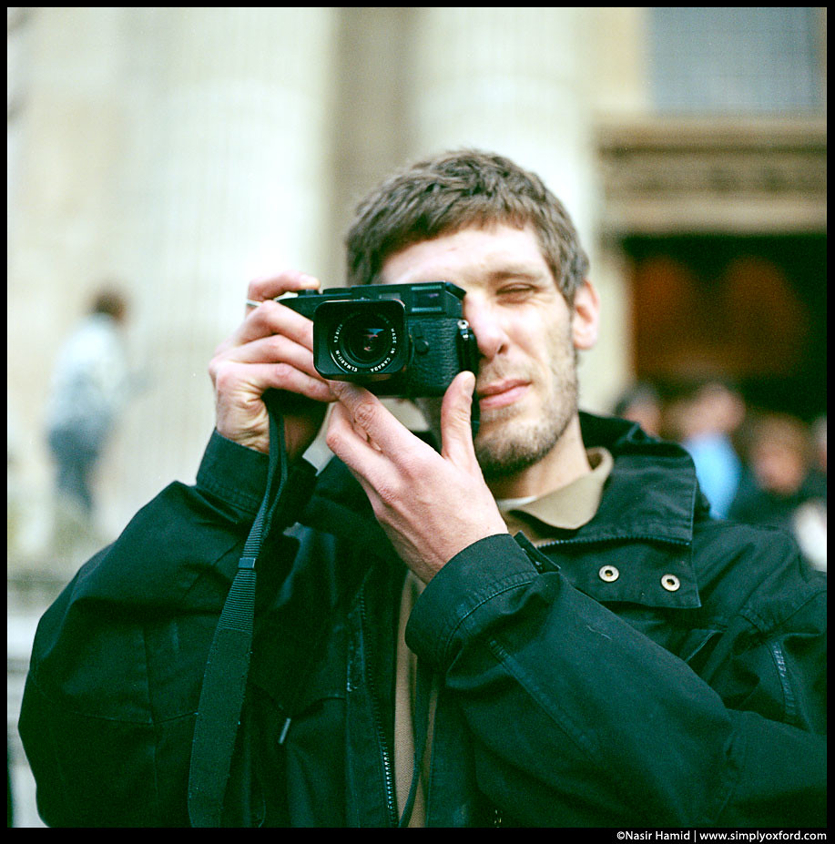 A man using a Leica film camera
