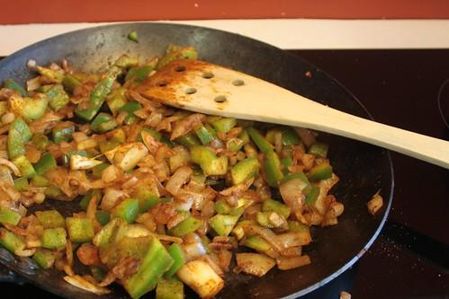 Photo of onions and peppers sauteing in a frying pan on a cook top.