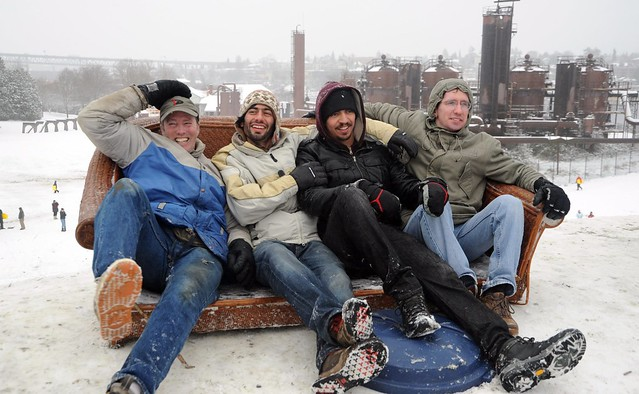 Smiling and celebrating, 4 guys in their sofa sled, couch surfing, winter wear, garbage can lid, on top of the hill, snow day, Gasworks Park, Wallingford, Seattle, Washington, USA
