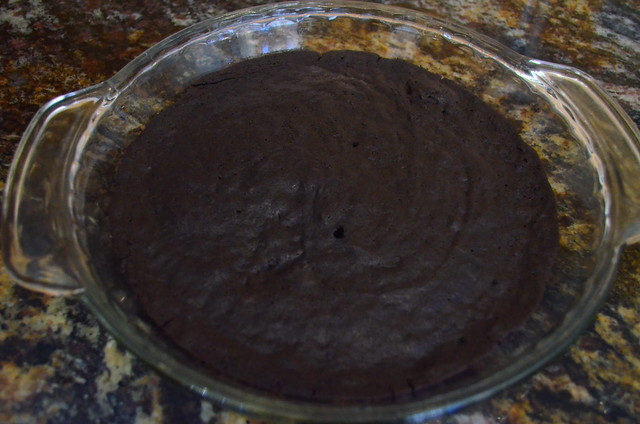 The brownie crust with a small hole in the middle, showing that it has finished baking.