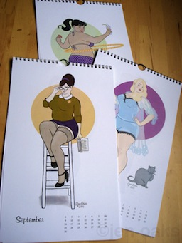 This image shows three calendars laid out on what looks like a wood table. Each of the calendars are opened up to a different page. The one on top, September, shows an illustration of a white woman with brown hair in a bun on top of her head sitting on top of a ladder. She's wearing librarian-style glasses, a green sweatshirt with a white collar, a short purple skirt, stockings, and black heels. She's holding a book in one of her hands. The calendar immediately underneath that one is only somewhat exposed, but you can make out a white blonde woman who is standing with her hands on her waist. She's wearing light blue