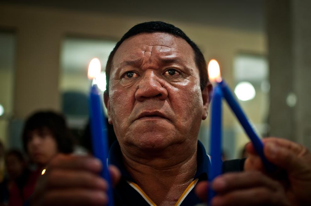 Un peregrino sosteniendo velas encendidas con ambas manos eleva sus oraciones a la Virgen durante los rezos en la capilla lateral de la basílica de Caacupé, en la noche del 7 de Diciembre. (Elton Núñez)