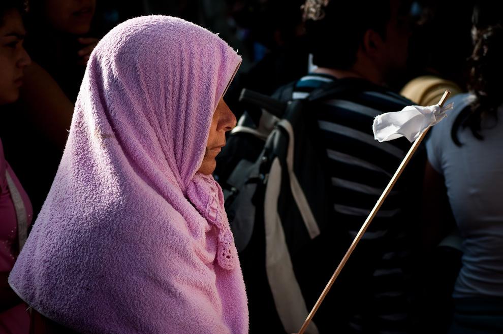 Una señora se protege del cálido sol de la mañana con una toalla mientras esperaba el momento para saludar a la imagen de la Virgen de Caacupé después de la misa central. (Elton Núñez)