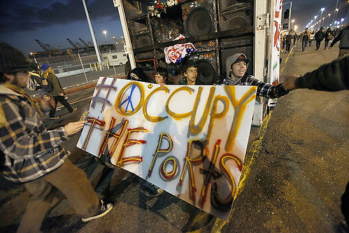 Several protesters ride on the back of a truck as thousands of Occupy Oakland protesters march to the Port of Oakland on Monday, Dec. 12, 2011 in Oakland, Calif. They were planning to stay until the next shift began at the port at 3 a.m. by Pan-African News Wire File Photos