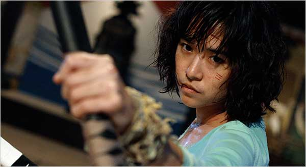 Zen, a young Asian woman, holds a bow staff of some sort and looks ready to fight