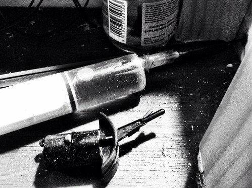 A black & white photograph of a syringe with a high amount of shadow