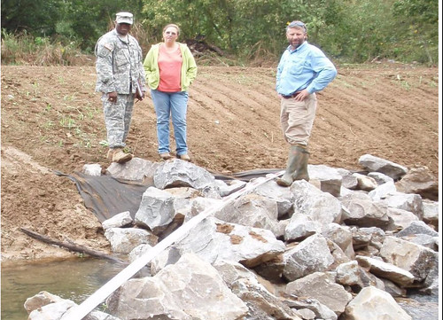 Earth Team Volunteer Sgt. Patrick Bower, Soil Conservationist Janet Coleman and District Conservationist Kevin Hart inspect a streambank protection jetty.