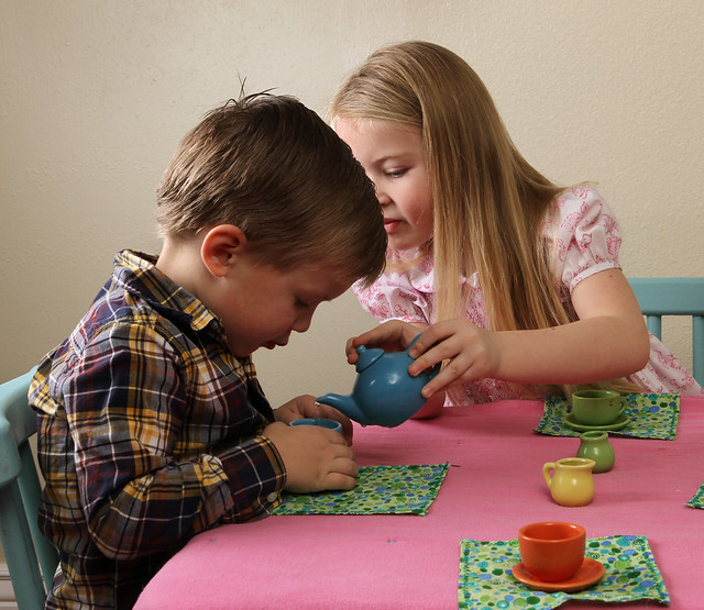 Serving her little brother - child tea party