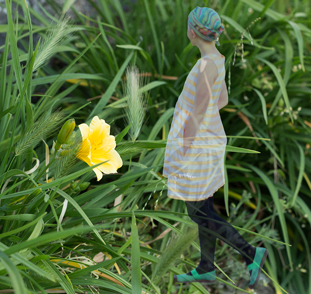 transparent girl in striped yellow dress, yellow flower and green grass