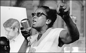 black and white photo of Ella Baker wearing sunglasses at a podium