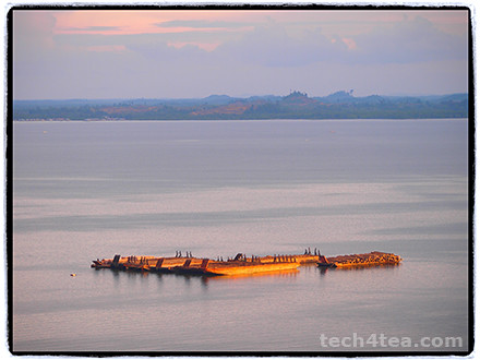 Barges in Sandakan port bathed in the golden light of the sunset. Taken with Olympus PEN E-P3 using Frame filter.