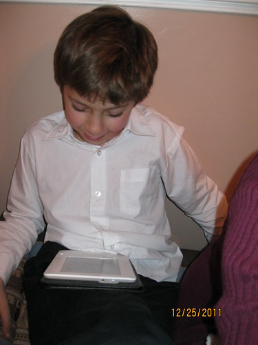 12/25/11:  Reading off his new Kindle (hand-me-down)