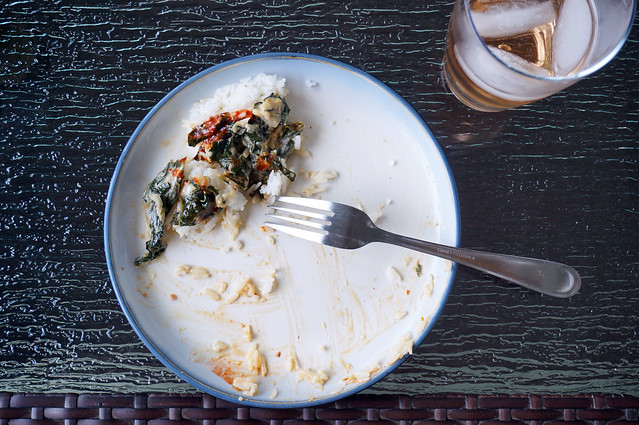 Seen from above, the plate of collards, now with only one big bite remaining. The fork sits, upturned, among the smears of light brown peanut sauce and bright red hot sauce.