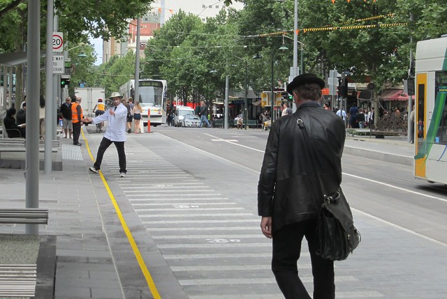 A pedestrian walks along the Swanston Street tram stop/bike lane