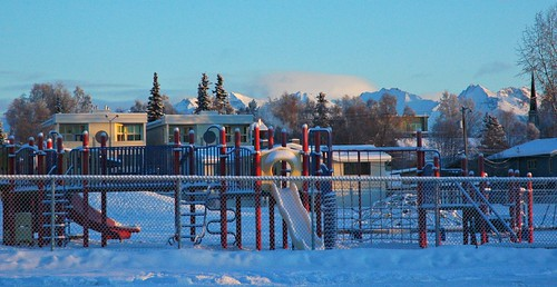 Childrens elementary school playground jungle gym under snow on Christmas Eve, clear blue sky, fence, Chugach Mountain Range, church steeple, trees, condos, South Addition, Anchorage, Alaska, USA by Wonderlane