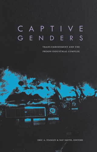 The cover of Captive Genders, which is black with a photo of cop cars on fire in blue