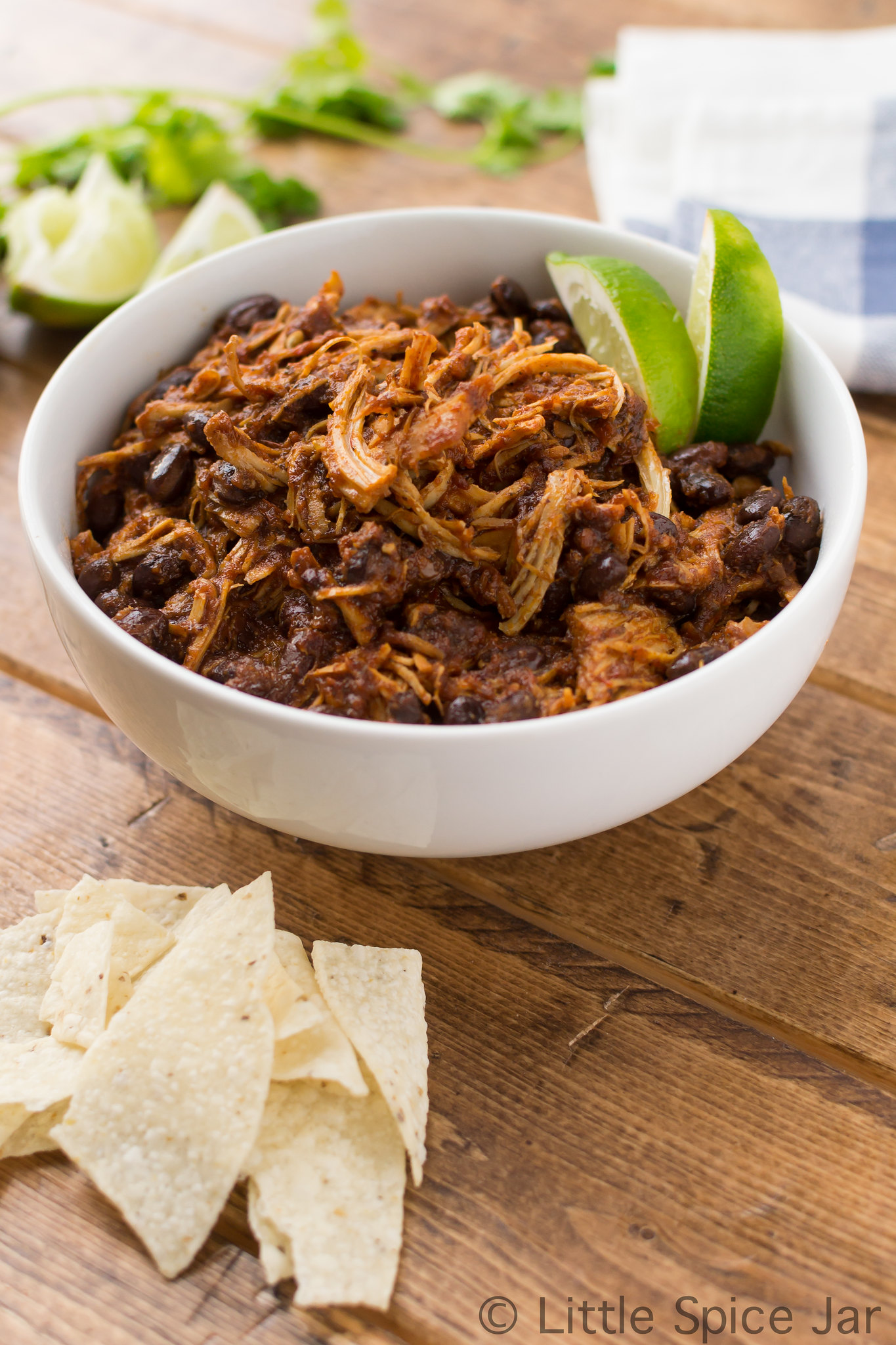 bowl of prepared shredded salsa chicken and black beans with tortilla chips and lime wedges