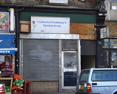 "An end-of-terrace shopfront with a plain metal shutter covering the shop window.  The sign above reads ""Croydon-Sosyal Yardimlasma Ve Dayanisma Dernegi"" and has a stylised rose drawn to one side.  This sign covers only part of the fascia; the rest is mainly bare wood.  A projecting sign reading ""CAFE 87"" is on one side.  The whole thing looks rather dilapidated."