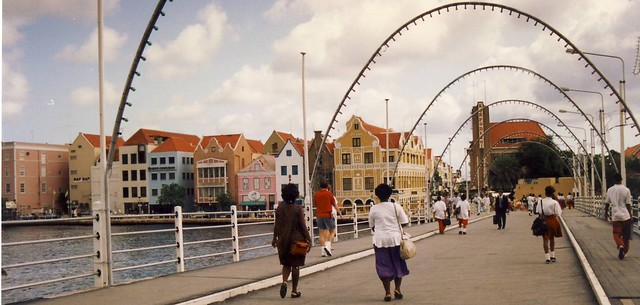Curacao: People walking across Queen Emma pontoon bridge in Willemstad, with pretty, colourful houses in the background