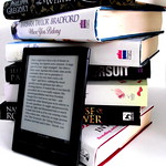 eReader next to stack of paper books
