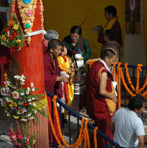 Sakya family members share a moment in the blessing line, Tibetan Buddhist monks, behind a brightly painted flower covered column, Long Life Blessing, Tharlam Monastery stage, Boudha, Kathmandu, Nepal by Wonderlane