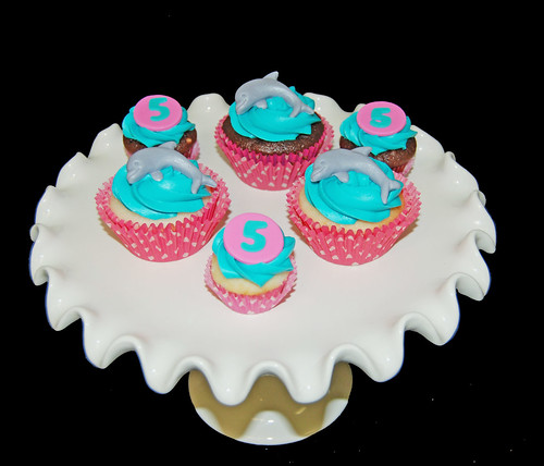 aqua and pink dolphin cupcakes with poink polka dot cupcake liners for a 5th birthday