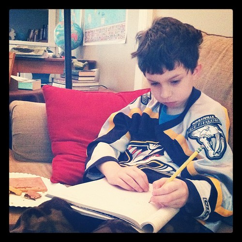 Spelling on the couch. Bed head. Camo pj's. Preds jersey. And a pop-tart. Love it. #homeschool #1000gifts #joydare