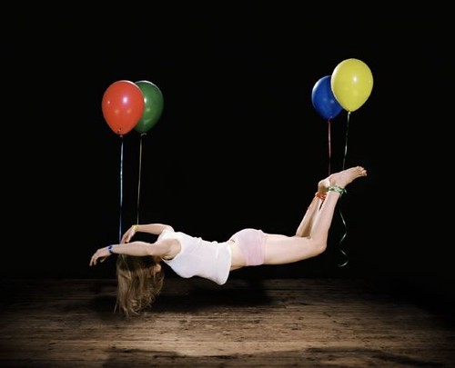 white woman suspended in mid-air by four balloons