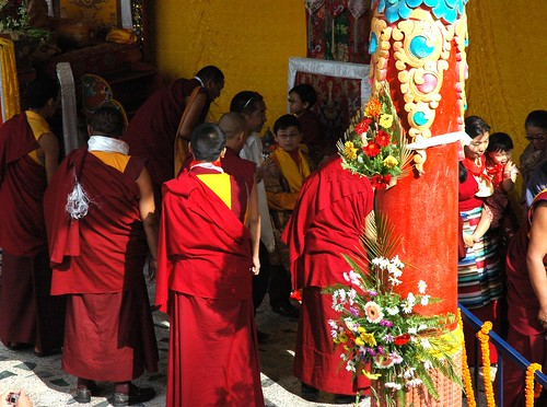 Sakya family members go through the blessing line attended by monks, behind the brightly painted flower covered column, Long Life Blessing, Tharlam Monastery stage, Boudha, Kathmandu, Nepal by Wonderlane