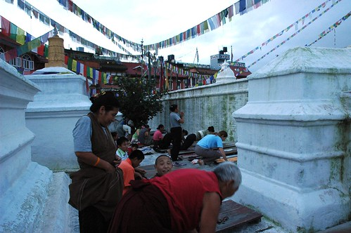 Hey - she is taking our picture - prostrators early in the morning on the public boards at The Great Stupa Jarung Kashor, people from around the world taking refuge, prayer flags, east side, Boudha, Kathmandu, Nepal by Wonderlane