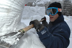 SAPPORO, Japan (Feb. 1, 2012) Aviation Electronics Technician Airman Trevor Teschel sheers away at a block of compressed snow as he helps create a snow sculpture with the Navy Misawa Snow Sculpture Team. (U.S. Navy photo by Senior Chief Mass Communication Specialist Daniel Sanford)