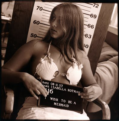 Black and white mugshot-style photo of a white woman aged 16. She is wearing a shell bra. The placard she's holding says I wish to be a mermaid