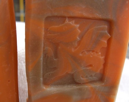 orange and brown swirled soap with a dragon stamp