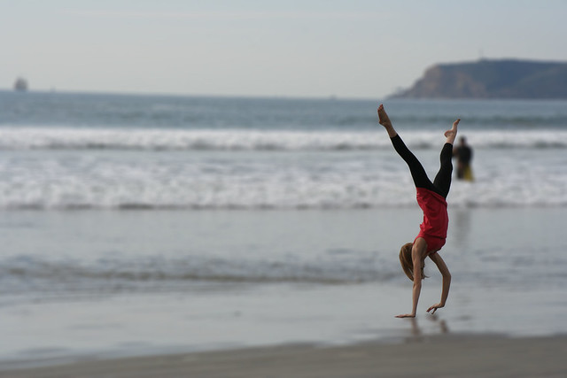 Woman doing a handstand on the beach