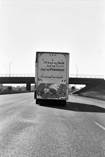 """Back of truck that reads: """"I'll keep my God and my guns and my freedom, you can keep the 'change'"""""""