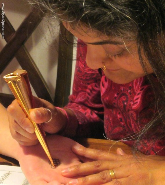 Sujatha applying mehndi design on Sheila's palm