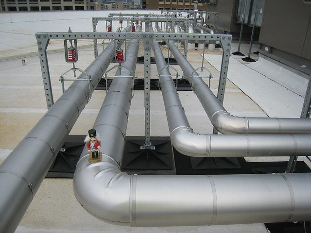Hundreds of feet of pipe circulate chilled and hot water throughout the new wing, including these pipes taking water to and from the rooftop air handling units.