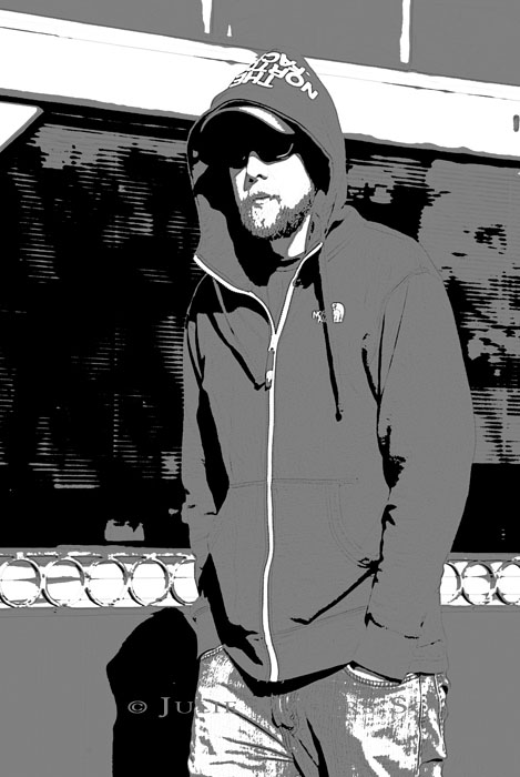 A graphic inspired black and white image of a hoodie cloaked young man gazing back at me from behind dark glasses in Fort Collins, Colorado.
