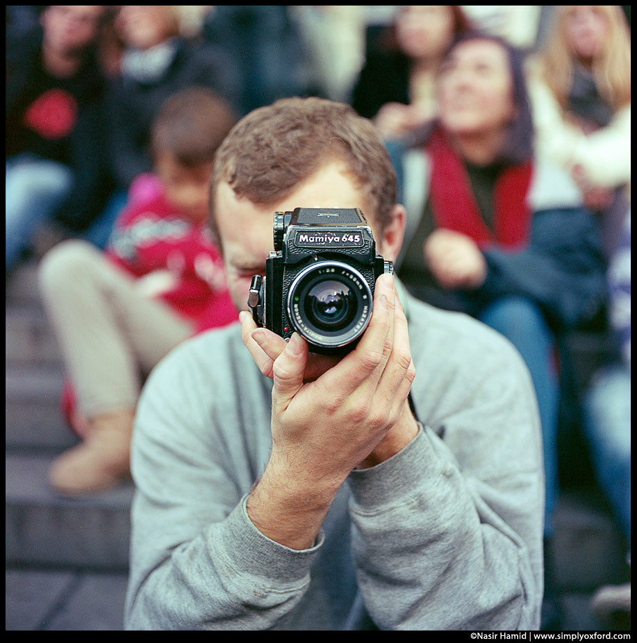A man using a Mamiya M645 film camera