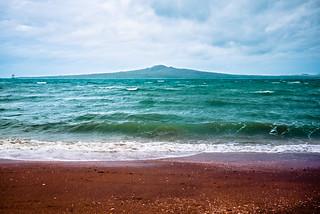 Изображение на Mission Bay Beach. newzealand beach strand waves auckland missionbay rangitoto