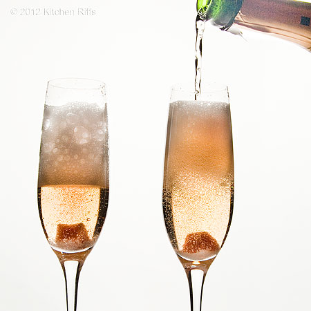 Pouring Champagne into 2 glasses of Champagne Cocktails