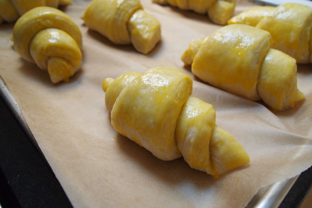 Proofed, egg-washed croissants