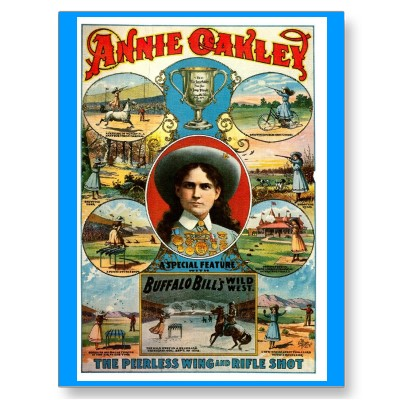 A photo of an original postcard advertising Buffalo Bill Cody's Wild West show featuring Annie Oakley's picture prominently in the middle, surrounded by other depictions of her doing spectacular feats of marksmanship.