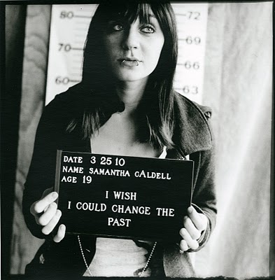 Black and white mugshot-style photo of a white woman aged 19. The placard she's holding says I wish I could change the past