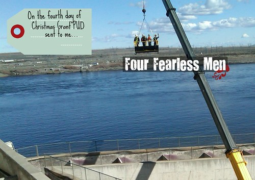 Four men suspended over the river in a crane