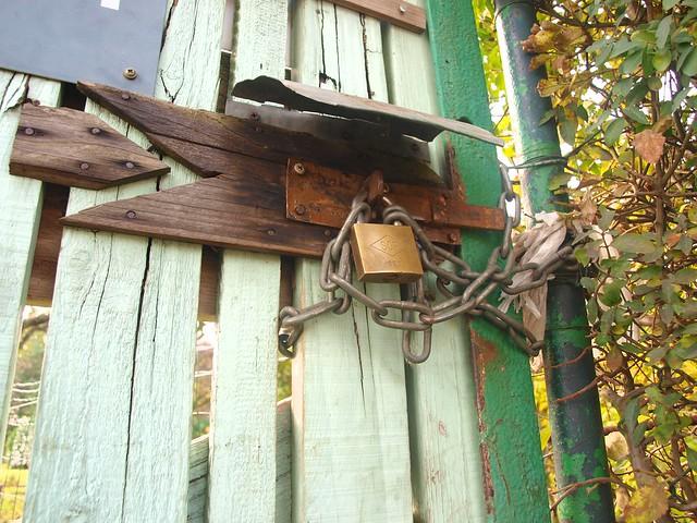 Photo en contre-plongée. Un cadenas enchaînant un loquet cloué sur du bois, fermant ainsi une porte en bois bleu-vert. L'encadrure de la porte est vert foncé et rouillé là où la peinture s'en va. Un bout de haie sur le côté droit et l'on aperçoit un jardin derrière. Oui, je paie Balzac pour écrire mes alt.
