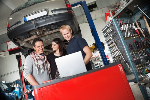 Couple in auto repair shop standing with mechanic
