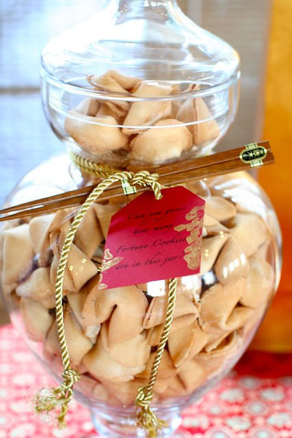 The jar's neck shows a gold rope accent with a pair of wood chopsticks and a red tag