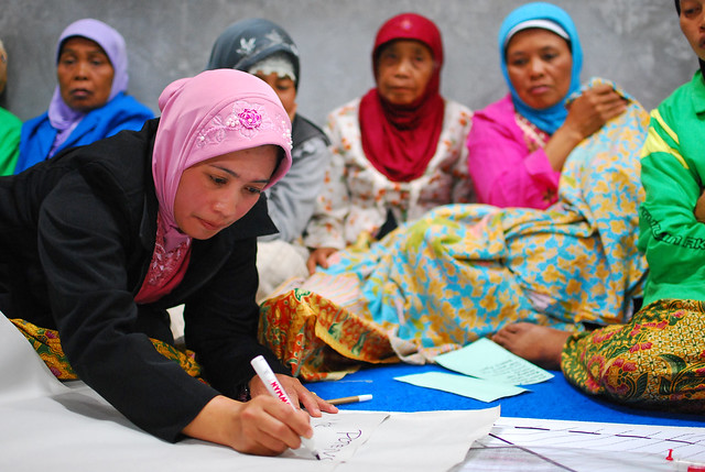 Women at a community meeting discuss the reconstruction of their village
