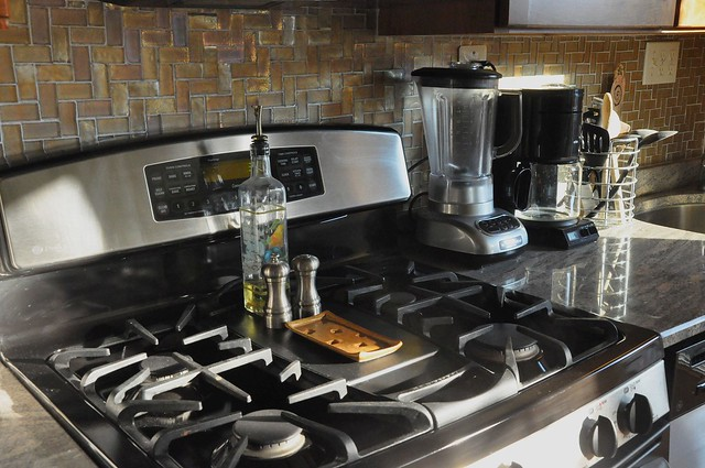 stainless steel stove, granite counter, glass tile